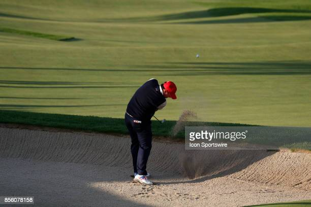 USA golfers Patrick Reed hits out of a bunker on the 4th hole during the third round of the Presidents Cup at Liberty National Golf Club on September...