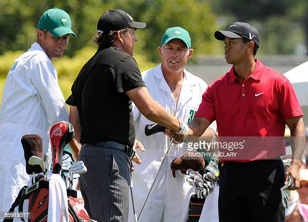 US golfers Phil Mickelson and Tiger Woods shake hands before teeing off on the first hole as their caddies Jim MacKay and Steve Williams look on...