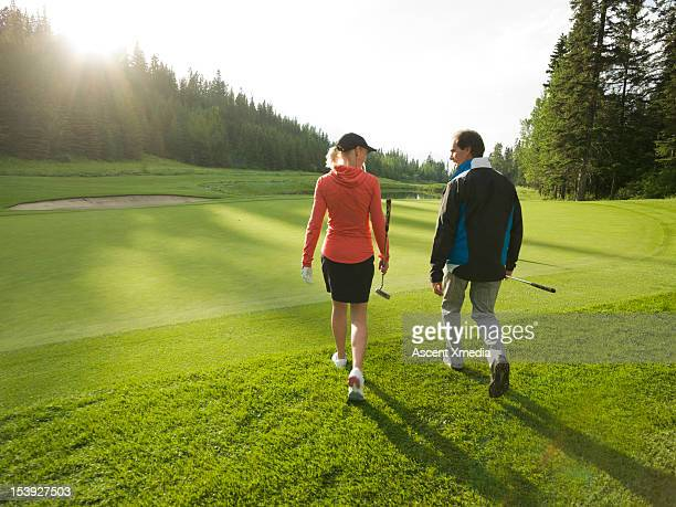 Golfers walk onto green with putters, sunrise