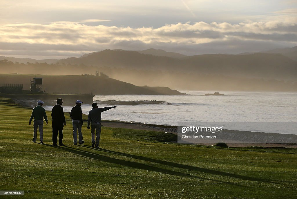 Golfers walk the 18th fairway during continuation of the first round of the ATT Pebble Beach National ProAm at Pebble Beach Golf Links on February 7...