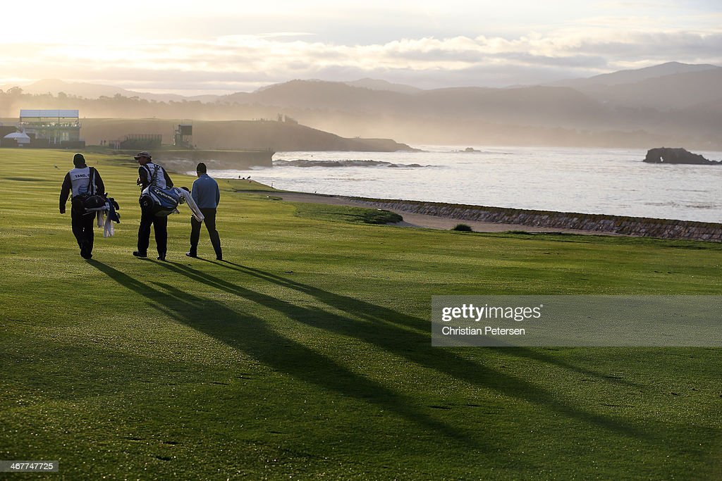 Golfers walk the 18th fairway during the continuation of the first round of the AT&T Pebble Beach National Pro-Am at Pebble Beach Golf Links on February 7, 2014 in Pebble Beach, California.