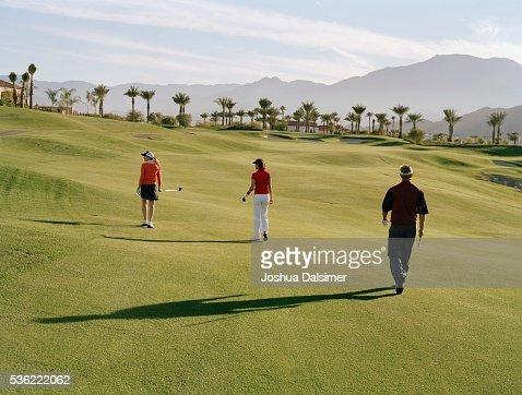 Golfers walking across golf course : Stock Photo