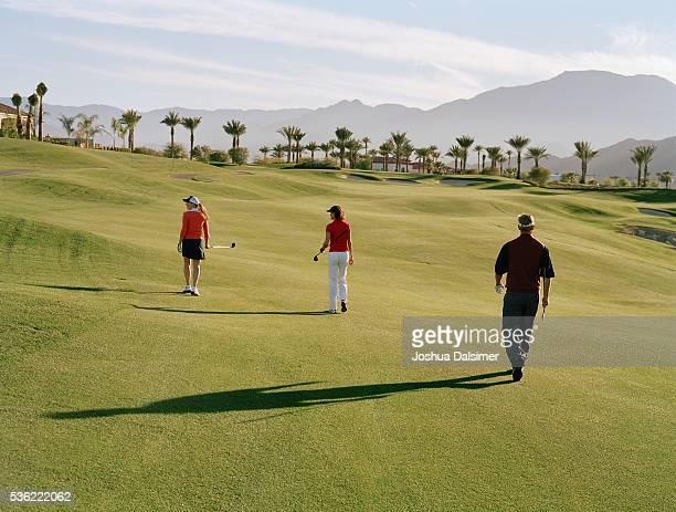 Golfers walking across golf course
