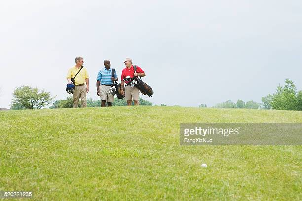 Golfers walking and talking on golf course
