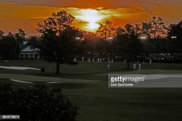 Golfers warm up on the practice range as the sun rises on the first day of practice for the 2017 Masters Tournament on April 3 at Augusta National...