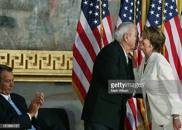 Golfing legend Arnold Palmer hugs House Minority Leader Rep Nancy Pelosi while Speaker of the House John Boehner looks on during a Congressional Gold...