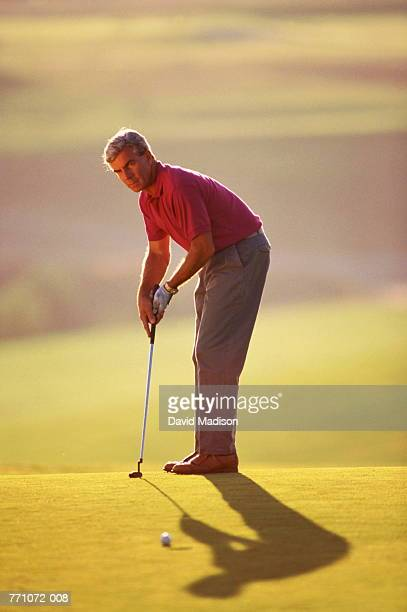 Golf,man in red polo shirt putting on green
