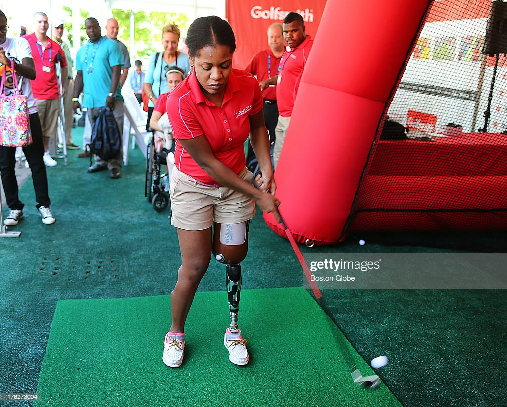 Golfsmith and Nike partnered with Spaulding Hospital's adaptive golf program to help marathon bombing victims get out on the links. Mery Daniels of Boston who lost a leg in the bombings hits a ball at the interactive swing zone driving range. Practice took place at the TPC Boston for the Deutsche Bank Championship, Aug. 28, 2013.