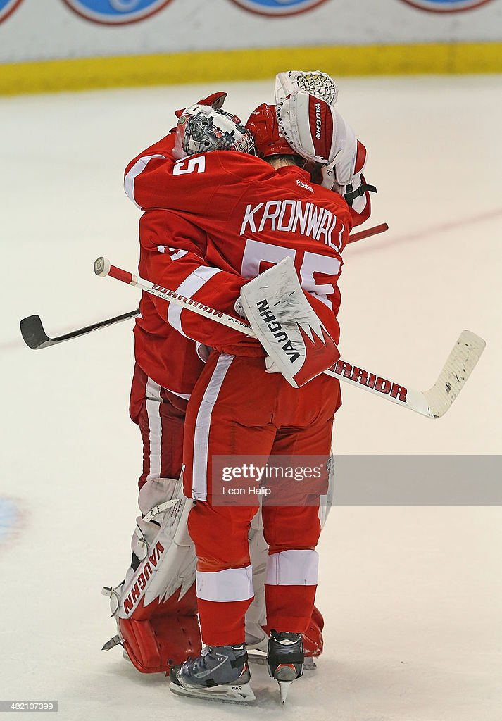 Golie Jimmy Howard #35 and Niklas Kronwell #55 of the Detroit Red Wings celebrate a win over the Boston Bruins at Joe Louis Arena on April 2, 2014 in Detroit, Michigan. The Wings defeated the Bruins 3-2.