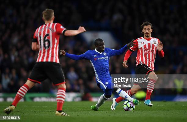 Golo Kante of Chelsea is watched by James WardProwse and Manolo Gabbiadini of Southampton during the Premier League match between Chelsea and...
