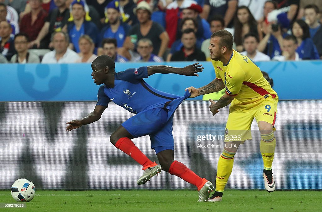 N'Golo Kante of France is pulled by Denis Alibec of Romania during the UEFA Euro 2016 Group A match between France and Romania at Stade de France on June 10, 2016 in Paris, France.