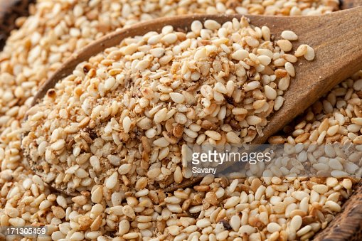 Gomasio seeds being scooped by wooden spoon