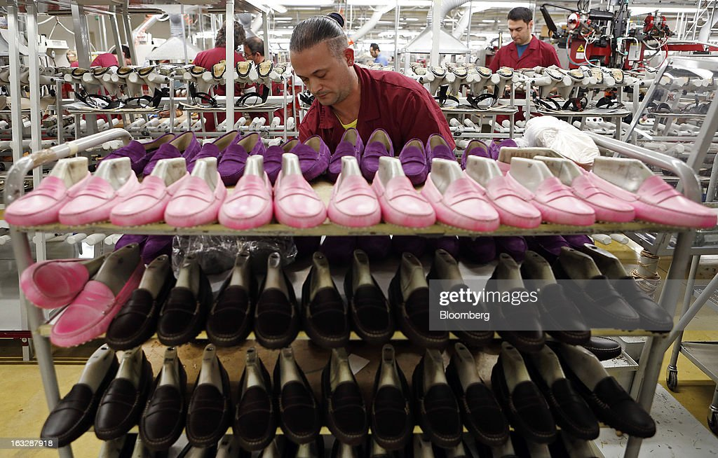 Gommino suede and leather moccasin loafers sit on a shelf during the manufacture of Tod's SpA luxury shoes inside the workshop at the company's...