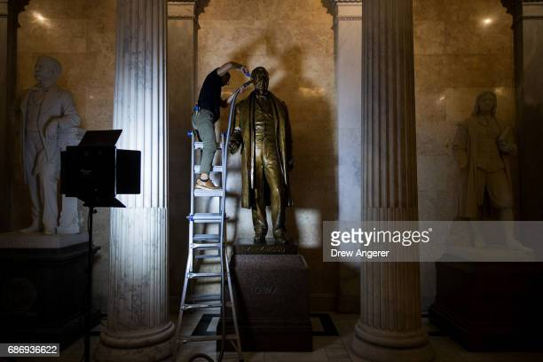 Gompo Yarmolinsky a staff member with the Architect of the Capitol cleans a statue of Samuel Kirkwood governor of Iowa during the Civil War and...