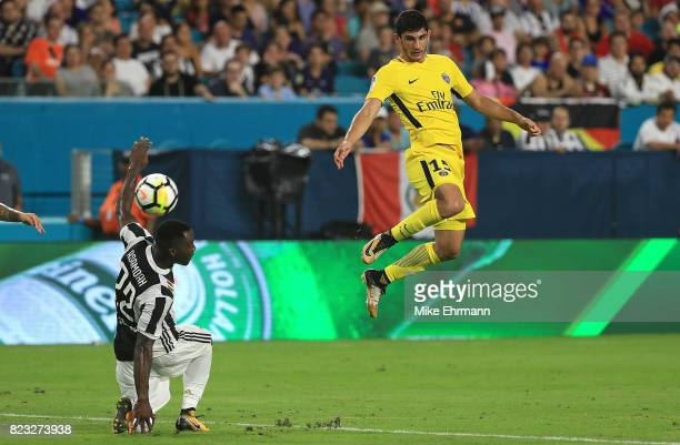 Goncalo Guedes of Paris SaintGermain shoots over Kwadwo Asamoah of Juventus during the International Champions Cup 2017 match at Hard Rock Stadium on...