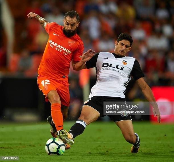 Goncalo Guedes of Valencia competes for the ball with Cifuentes of Malaga during the La Liga match between Valencia and Malaga at Estadio Mestalla on...