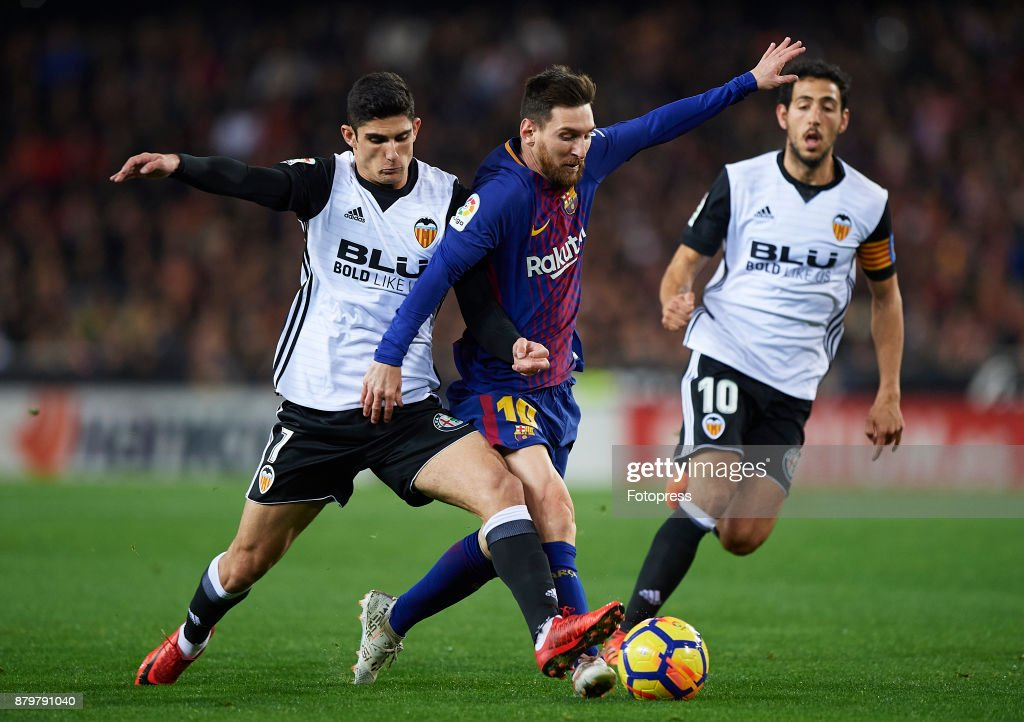 Goncalo Guedes of Valencia competes for the ball with Lionel Messi (R) of Barcelona during the La Liga match between Valencia and Barcelona at Estadio Mestalla on November 26, 2017 in Valencia, Spain.
