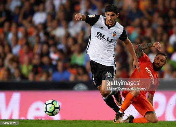 Goncalo Guedes of Valencia is tackled by Cifuentes of Malaga during the La Liga match between Valencia and Malaga at Estadio Mestalla on September 19...