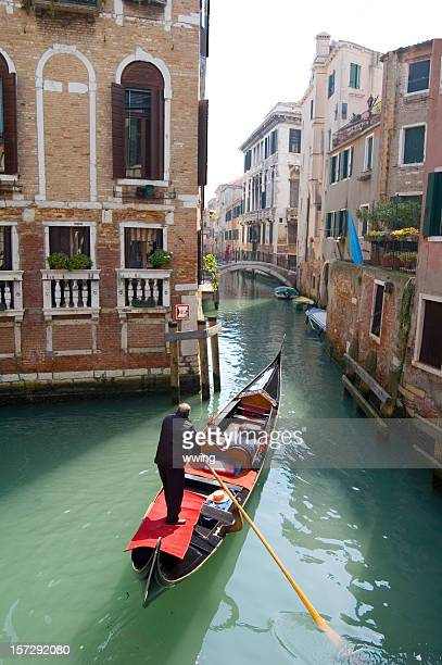 Gondola in Venice going down a small residential canal