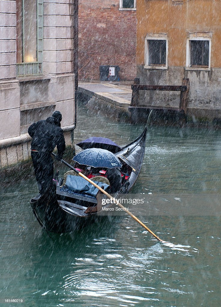 A Gondola sail in a small canal behind Saint Mark's Square during heavy snow on February 11, 2013 in Venice, Italy. Heavy snow, High water, wind and rain has been forcasted for today.