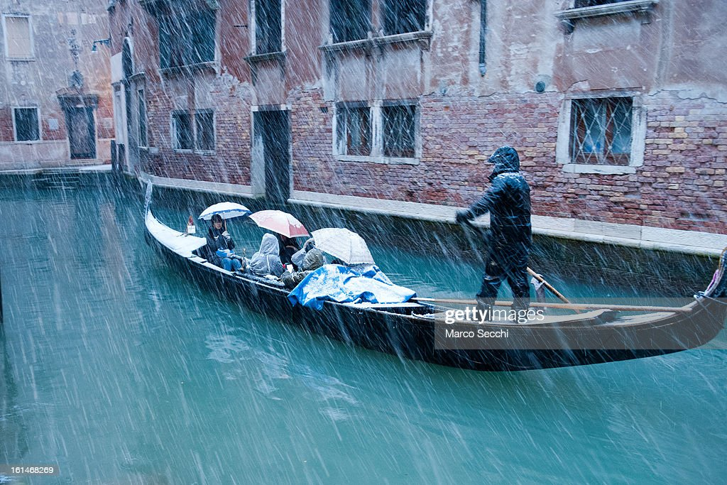 A Gondola sail in a small canal behind Saint Mark's Square during heavy snow on February 11, 2013 in Venice, Italy. Heavy snow, High water, wind and rain has been forecasted for today.