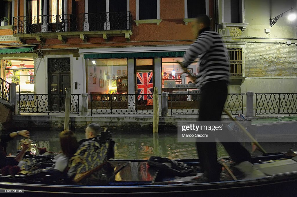 A gondola sails along a canal where a shop displays British flags and royal wedding memorabilia ahead of the royal wedding on April 29, 2011 in Venice, Italy. The wedding of Britain's Prince William and Kate Middleton took place at Westminster Abbey in London.