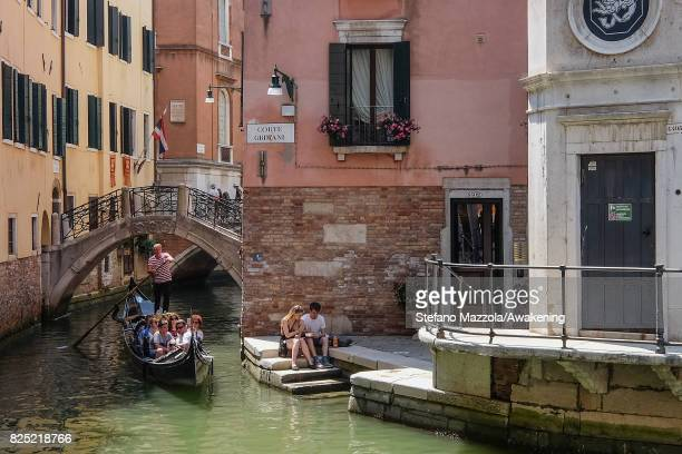A gondola sails on a canal in front of two tourists having lunch on the bank on August 1 2017 in Venice Italy Over 30 million tourists visit the 3...