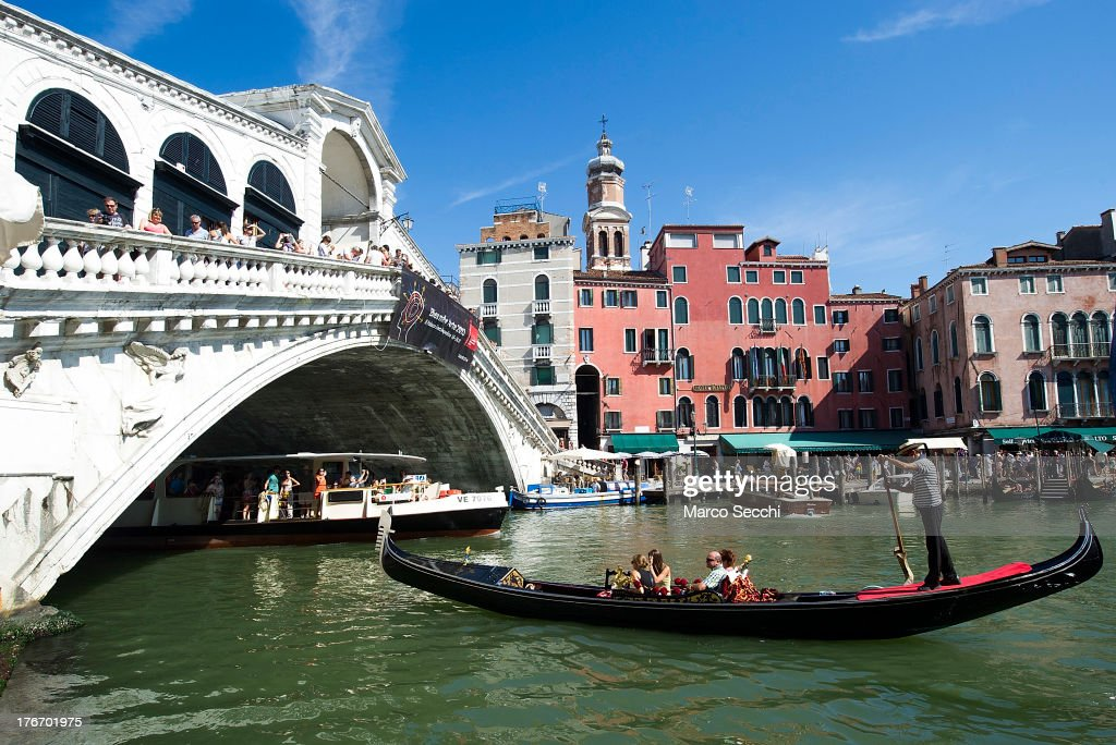 Gondola sails under Rialto Bridge in front of the same pontoon where few hours earlier a German tourist was crashed to death on August 17, 2013 in Venice, Italy. A German tourist was crushed to death on Saturday when the gondola he was boarding collided with a waterbus (Vaporetto) along Venice's Grand Canal.