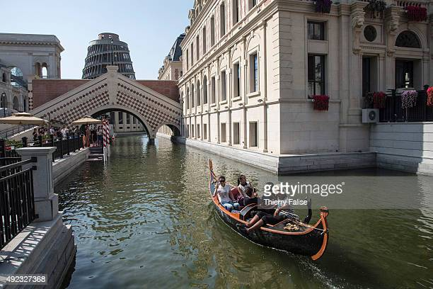 A gondola takes tourists on a canal along a replica of Europeanstyle houses and a Babel Tower at Dalian's 'City of Water' The City of Water also...