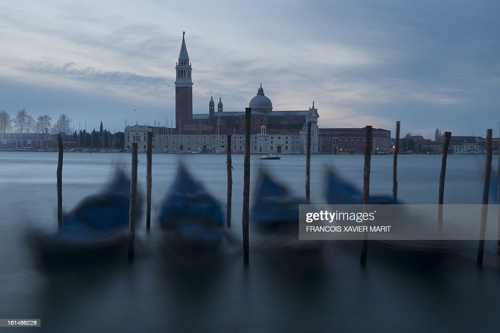 Gondolas are at quay early on February 8, 2013 near St Mark's square with San Giorgio Maggiore in the background during the carnival in Venice. The 2013 edition of the Venice carnival is untitled Live in Colour' and runs from January 26 to February 12.