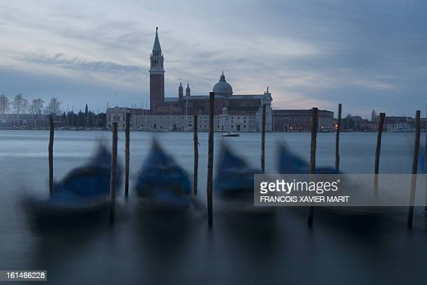 Gondolas are at quay early on February 8 2013 near St Mark's square with San Giorgio Maggiore in the background during the carnival in Venice The...