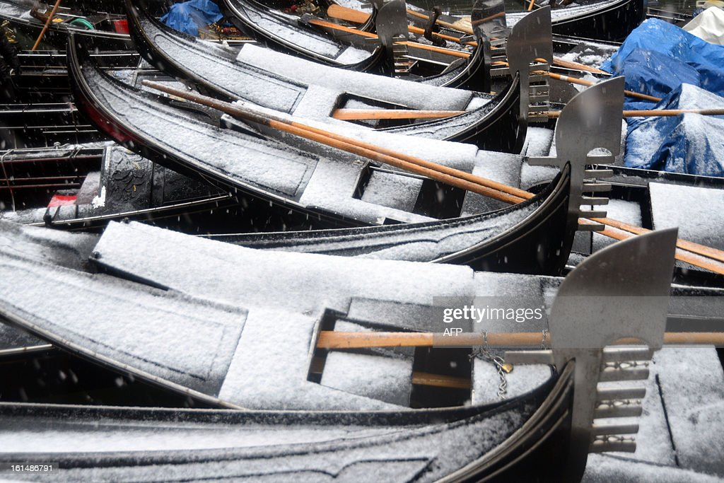 Gondolas are covered with snow during the carnival on February 11, 2013 in Venice. The 2013 edition of the Venice carnival is untitled ' Live in Colour' and runs from January 26 to February 12. AFP PHOTO / ANDREA PATTARO