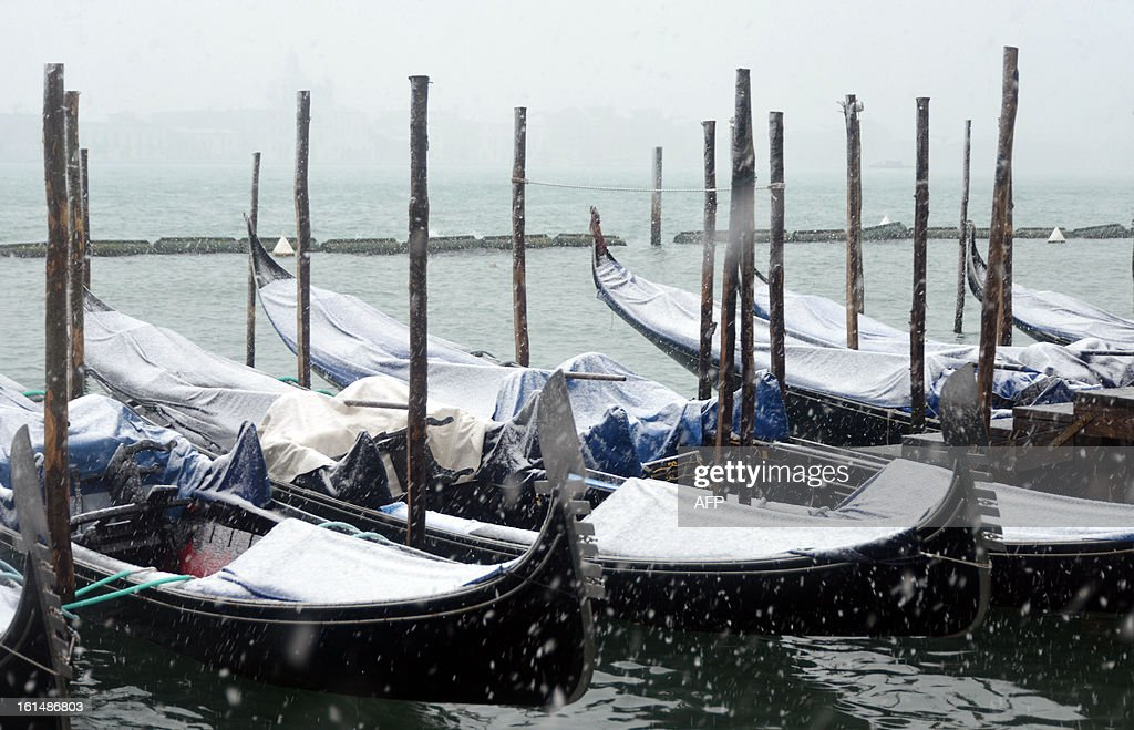 Gondolas are covered with snow during the carnival on February 11, 2013 in Venice. The 2013 edition of the Venice carnival is untitled ' Live in Colour' and runs from January 26 to February 12.