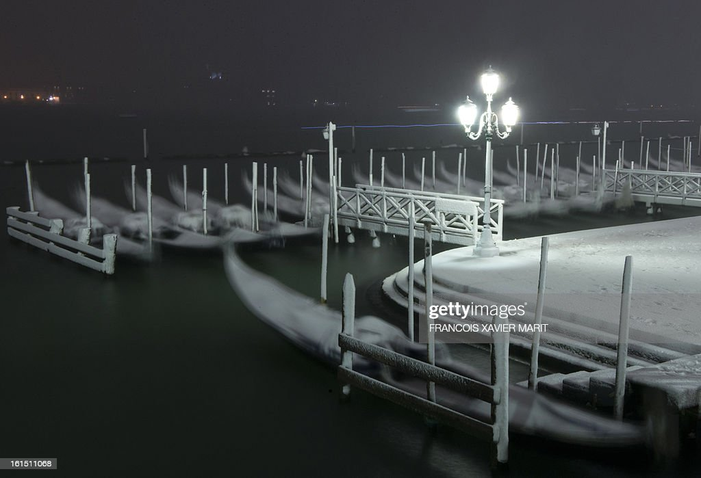 Gondolas are covered with snow during the carnival on February 11, 2013 in Venice. The 2013 edition of the Venice carnival is untitled 'Live in Colour' and runs from January 26 to February 12. AFP PHOTO / FRANCOIS XAVIER MARIT
