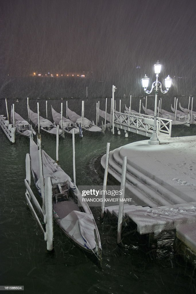 Gondolas are covered with snow during the carnival on February 11, 2013 in Venice. The 2013 edition of the Venice carnival is untitled 'Live in Colour' and runs from January 26 to February 12.