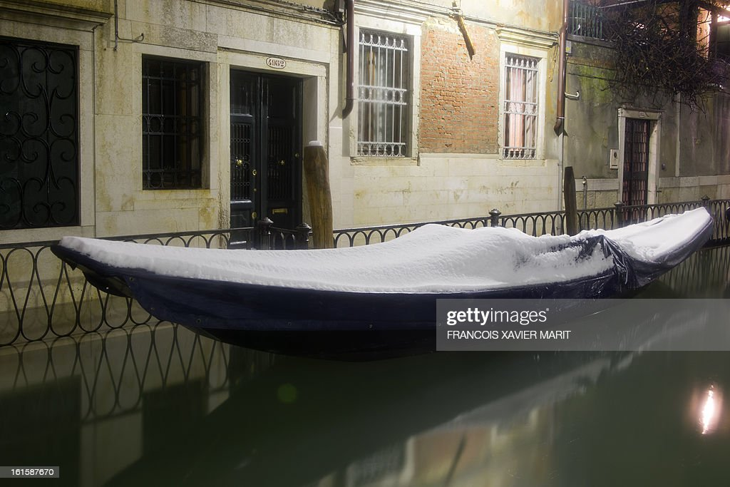 Gondolas are covered with snow during the carnival on February 11, 2013 in Venice. The 2013 edition of the Venice carnival is untitled ' Live in Colour' and runs from January 26 to February 12. AFP PHOTO / FRANCOIS XAVIER MARIT