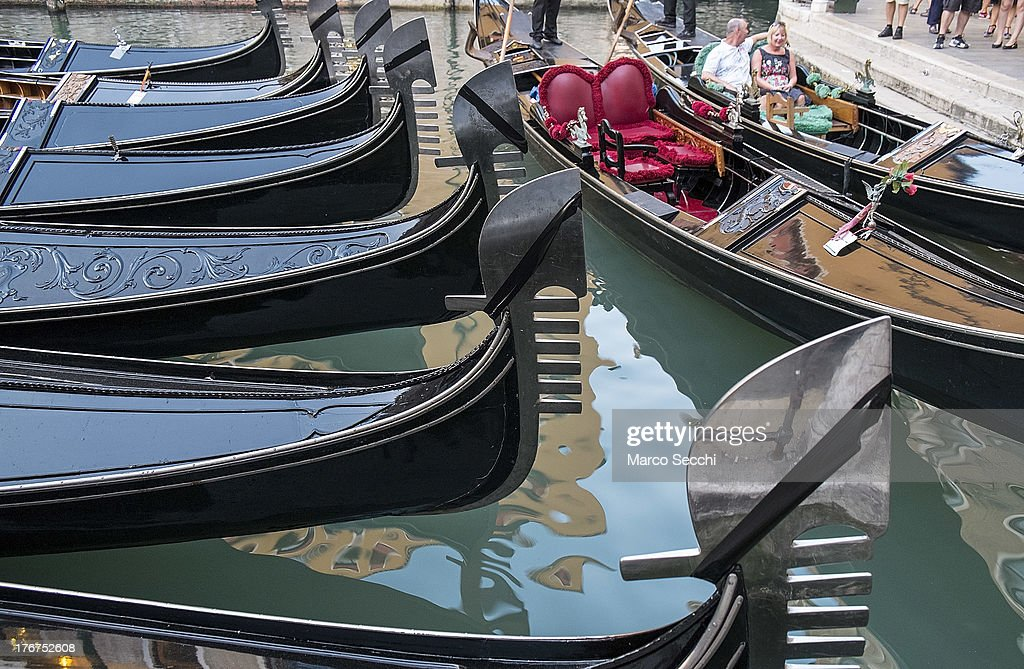 Gondolas draped in mourning are seen in Bacino Orseolo where on August 17 a German tourist was killed on August 18, 2013 in Venice, Italy. A German tourist was crushed to death on Saturday when the gondola he was boarding collided with a waterbus (Vaporetto) along Venice's Grand Canal.