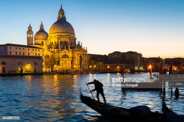 Gondolier at dusk on the Grand Canal. Venice, Italy.