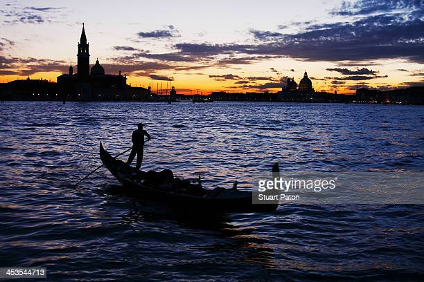 Gondolier at twilight in Venice.