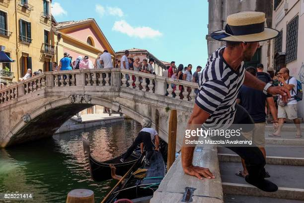 A gondolier jumps from his gondola to the bank on August 1 2017 in Venice Italy Over 30 million tourists visit the 3 mile by 2 mile city of Venice...