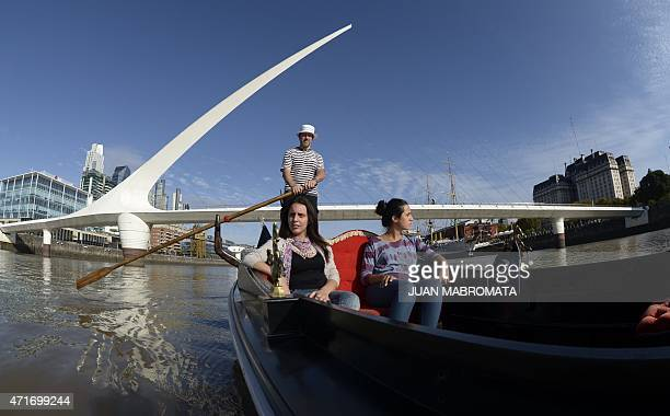 A gondolier moves a Venetian gondola with tourists with the 'Puente de la Mujer' in the background during a tour through Puerto Madero in Buenos...