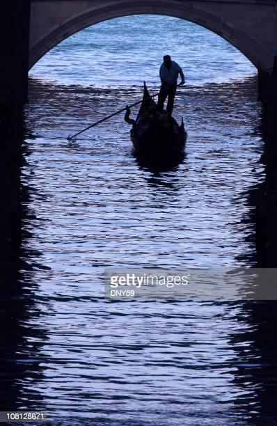 Gondolier Navigating Gondola Under Archway in Venice Canal