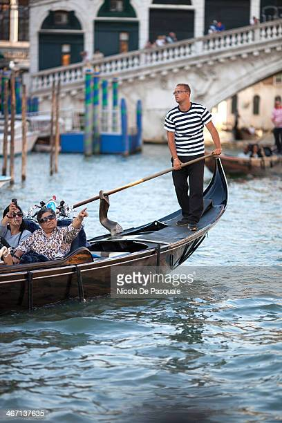 CONTENT] Gondolier riding gondola on Grand Canal and showing Venice to a group of tourists Rialto Bridge and some Italian buildings on background