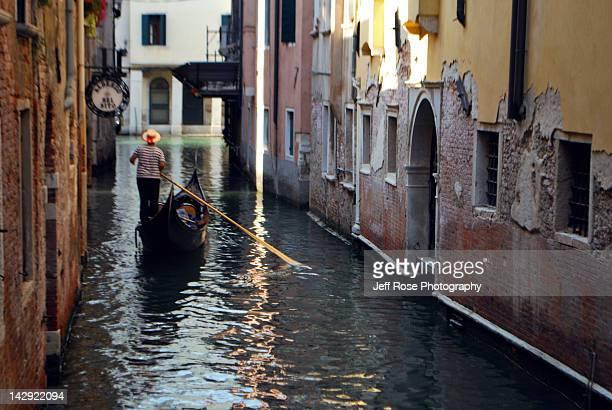 Gondolier rowing gondola in canal