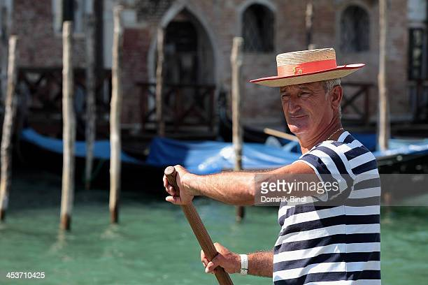 Gondolier rows a gondola in Grand Canal on August 18 2013 in Venice Italy