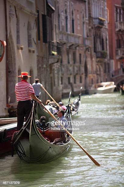 CONTENT] Gondoliers riding gondolas in narrow canal and showing the city to groups of tourists visiting Venice Some Italian apartment buildings on...