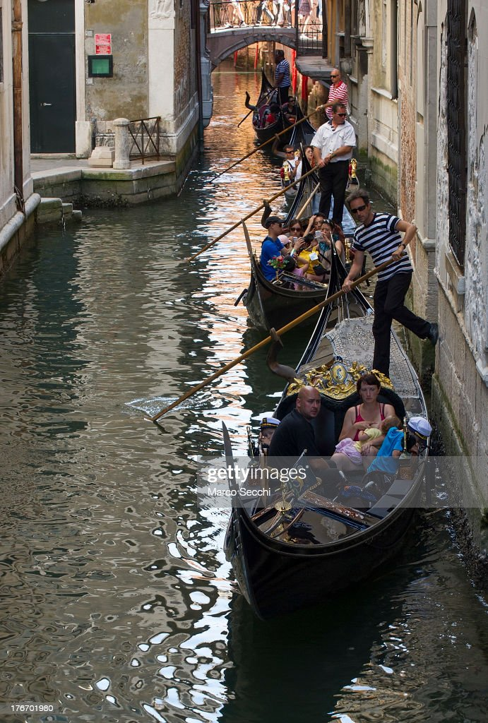 Gondoliers sail along a minor canal near Rialto where today a German tourist was crashed to death on August 17, 2013 in Venice, Italy. A German tourist was crushed to death on Saturday when the gondola he was boarding collided with a waterbus (Vaporetto) along Venice's Grand Canal.