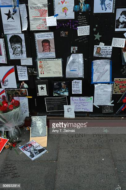 'Gone but never forgotten our hero' is written on the pavement below posters drawings and letters are mounted on a wall to the right of the flowers...
