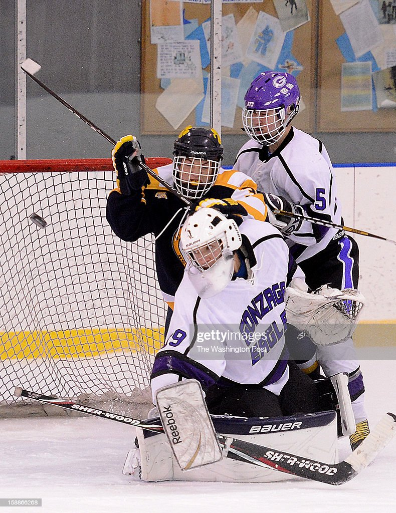 Gonzaga goalie Nick Platais knocks away the puck as St. Ignatius forward Riley Ells and Gonzaga defender Henry Chastain collide into him during the championship game of the Purple Puck National Capital Hockey Tournament hosted by Gonzaga College High School on Monday, December 31, 2012. St. Ignatius (Cleveland, OH) defeated Gonzaga 2-1 for the title.