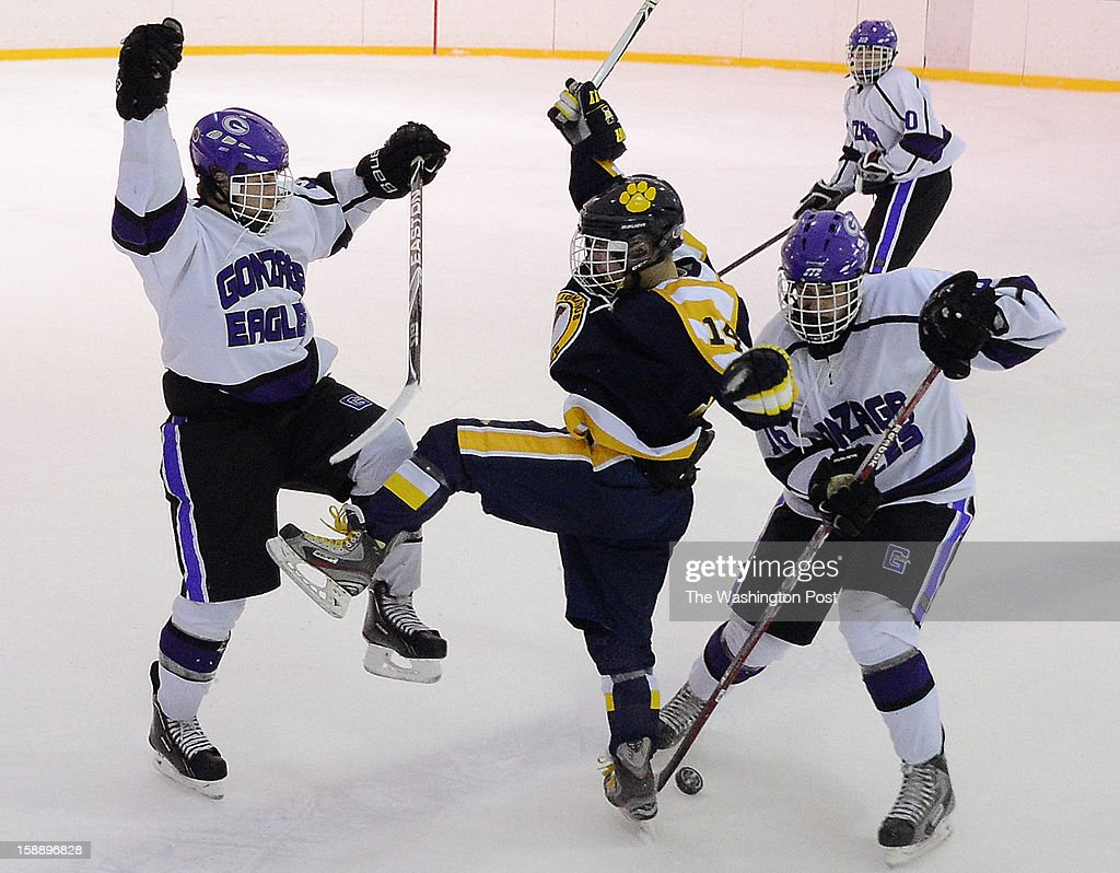 Gonzaga's Chris Meloni, left, and Owen Fisher, right, combine to steal the puck away from St. Ignatius's Jack Wiegandt during the championship game of the Purple Puck National Capital Hockey Tournament hosted by Gonzaga College High School on Monday, December 31, 2012. St. Ignatius (Cleveland, OH) defeated Gonzaga 2-1 for the title.